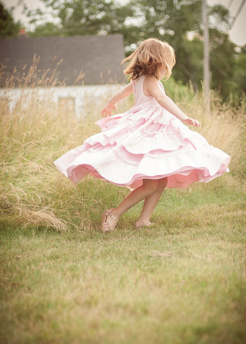 Girl twirling pink dress in a country field