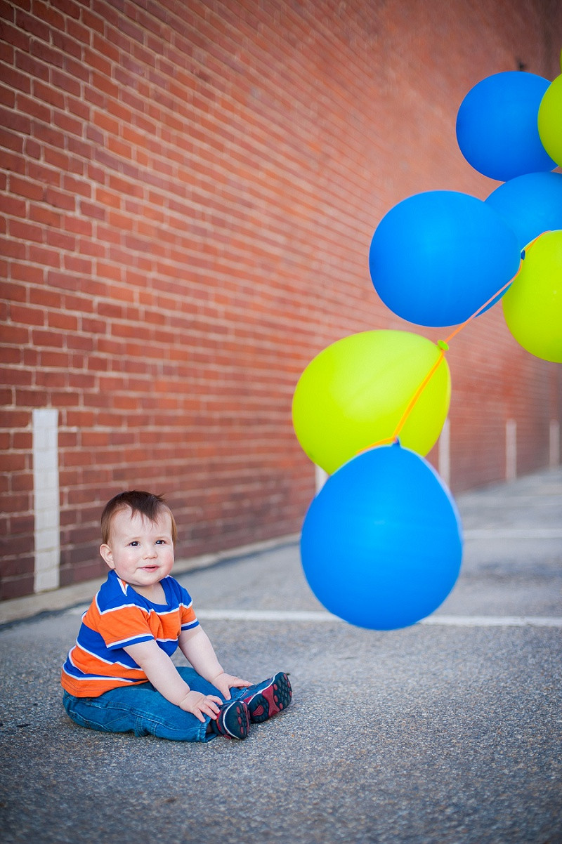 One year old with balloons next to brick wall