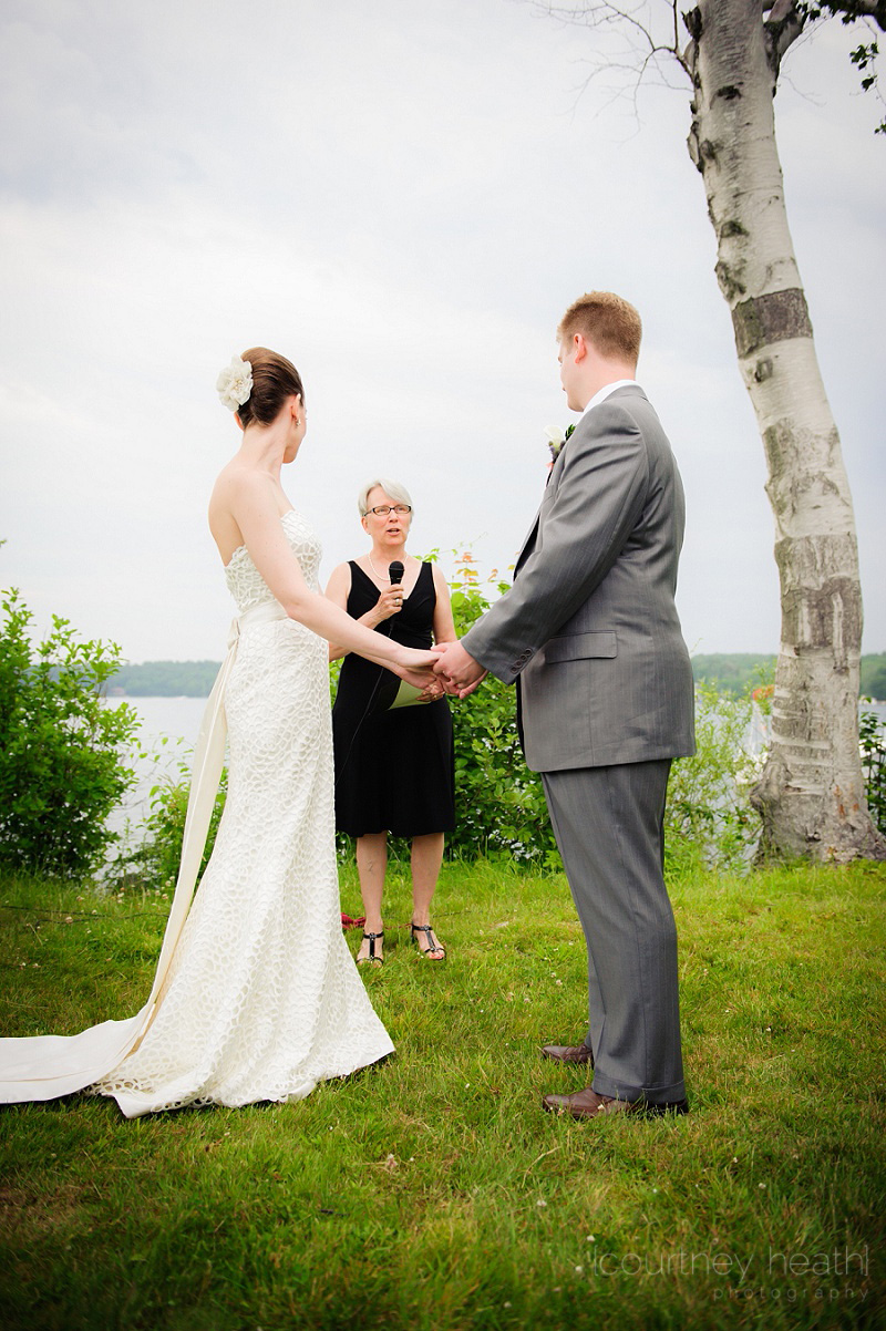 Bride and groom holding hands during wedding ceremony Lake Winnipesaukee