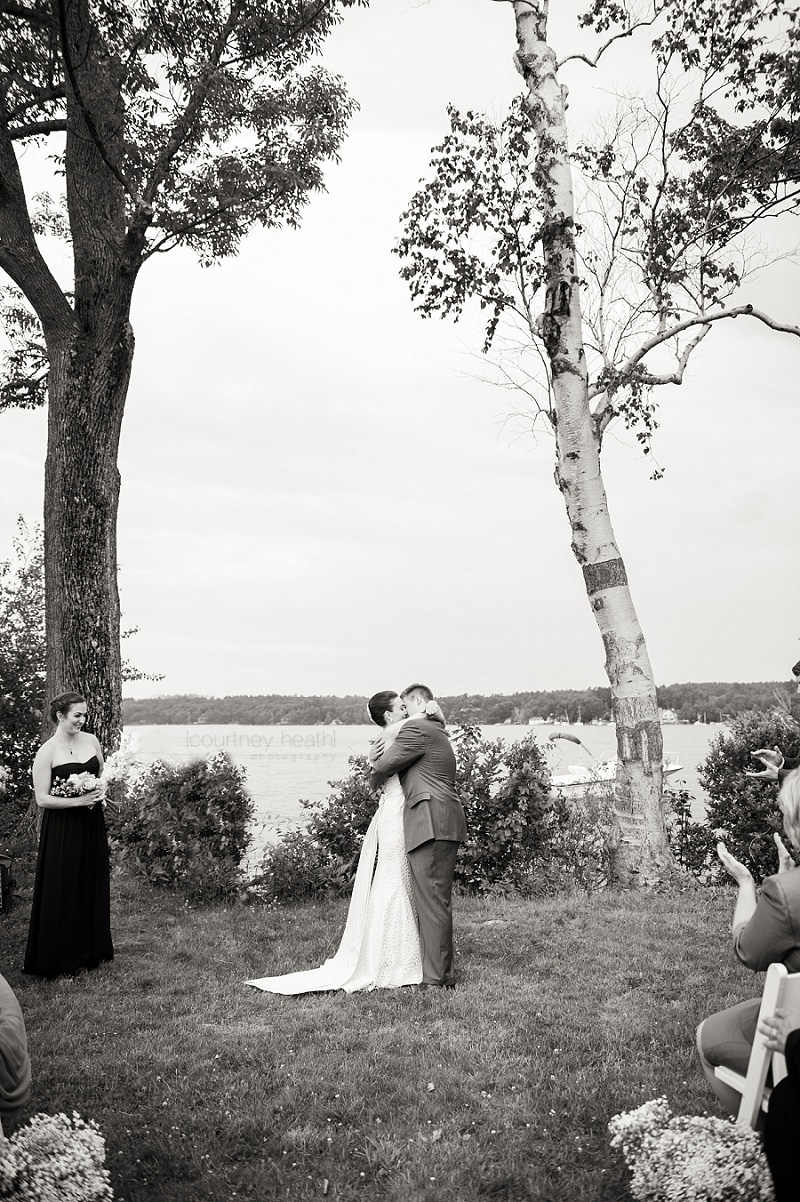 Black and white bride and groom first kiss in front of Lake Winnipesaukee