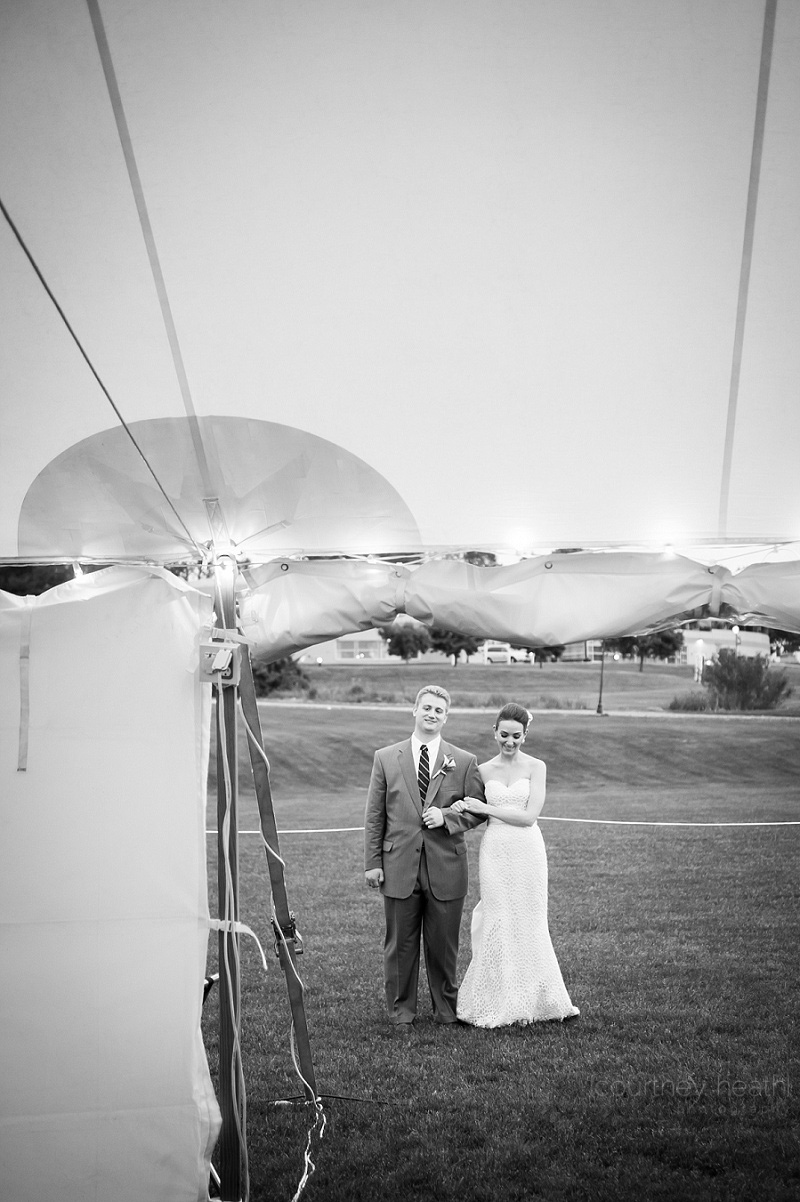 Bride and groom embrace arm in arm outside reception tent