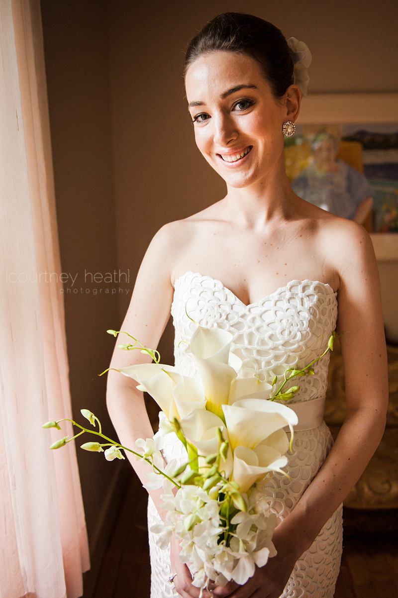 Bride smiling holding calla lily bouquet