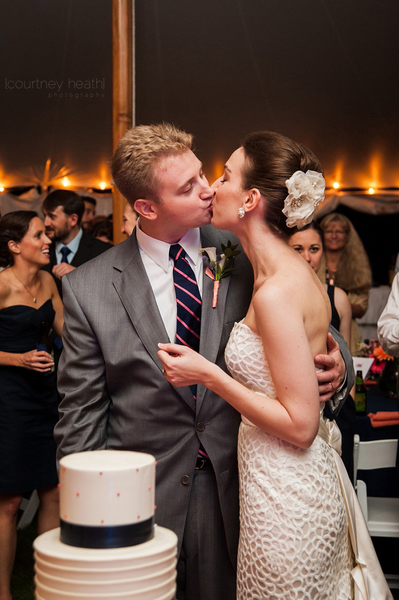 Groom and bride kiss in front of wedding cake