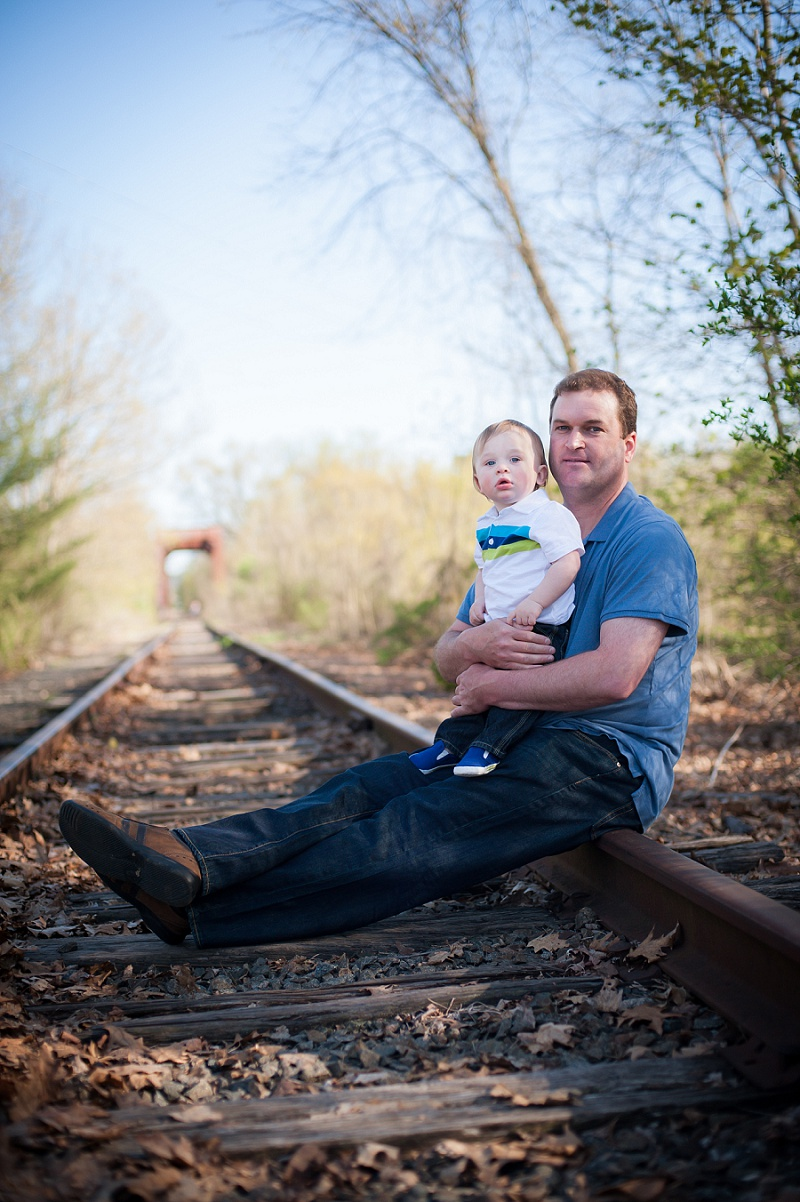 Father holding son sitting on train tracks
