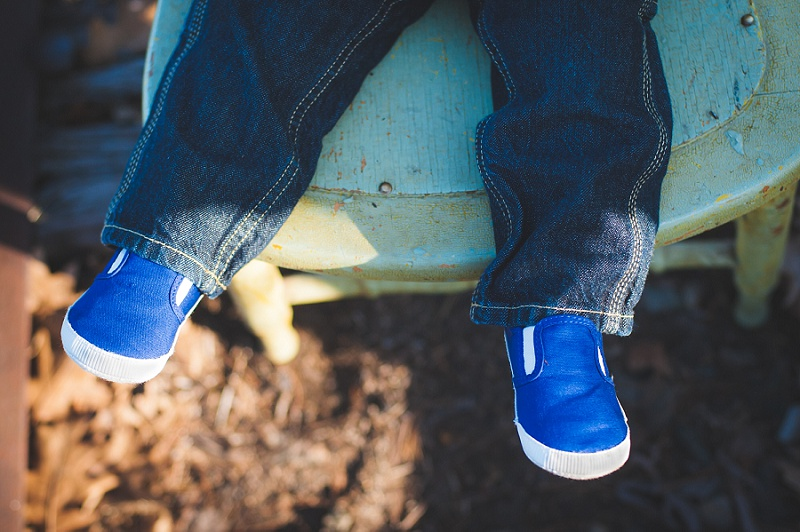 Boy's blue shoes on vintage chair