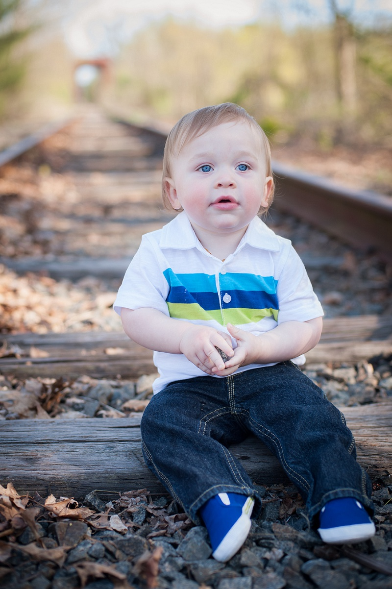 Blue eyed boy sitting on train tracks
