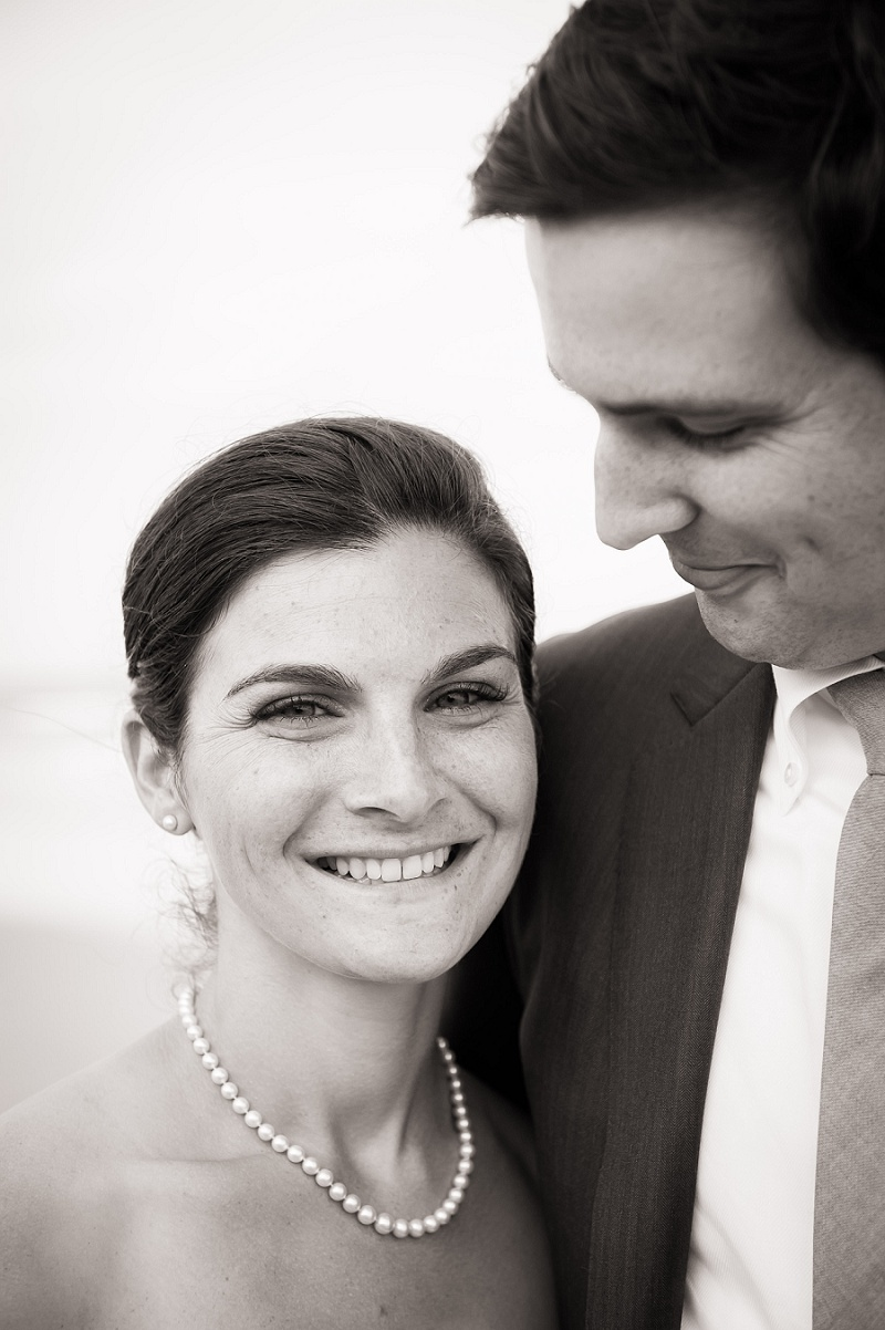 Bride smiling with groom looking down at her black and white