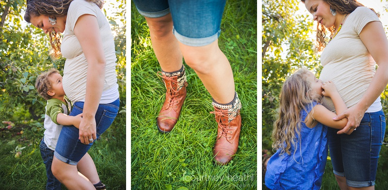 Pregnant woman in apple orchard wearing boots, children kissing belly