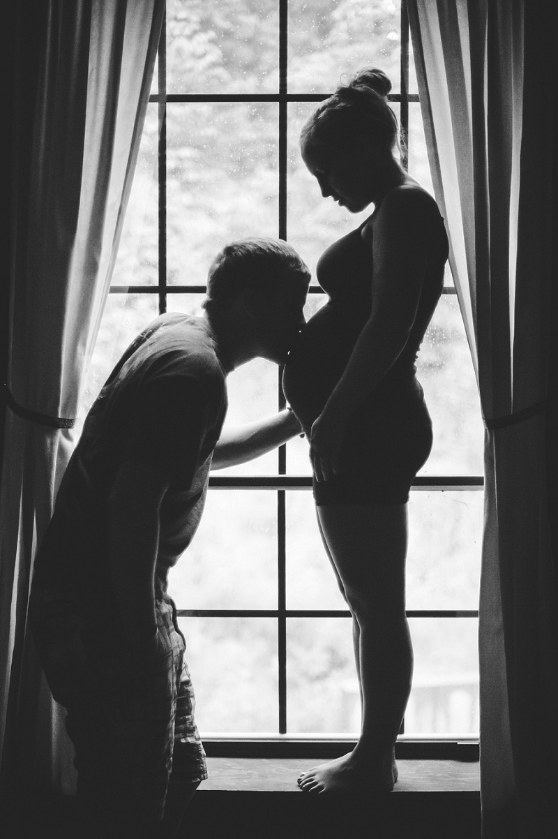 Black and white silhouette of pregnant woman and man kissing her belly