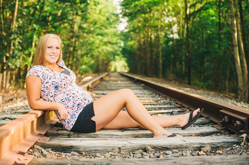 Pregnant mother sitting on railroad tracks