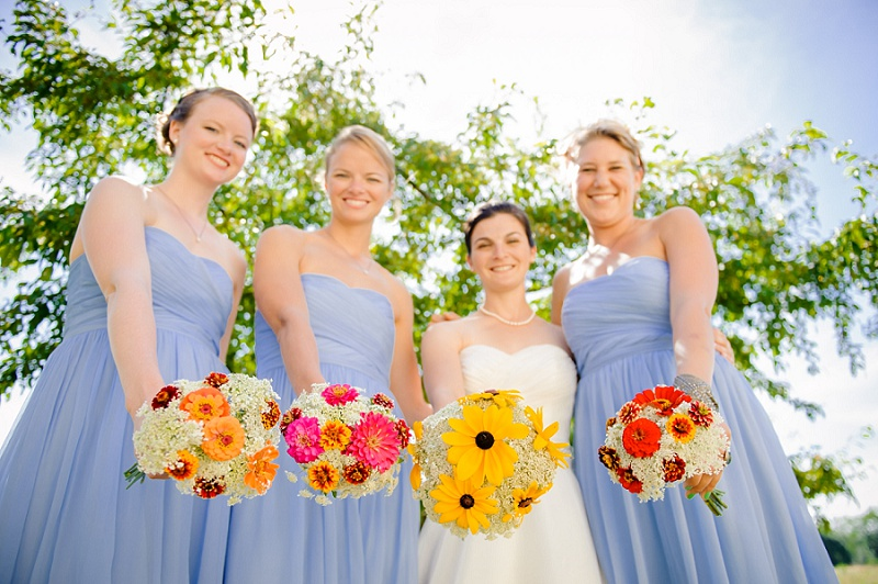 Bride and bridesmaids showing their colorful bouquets and smiling