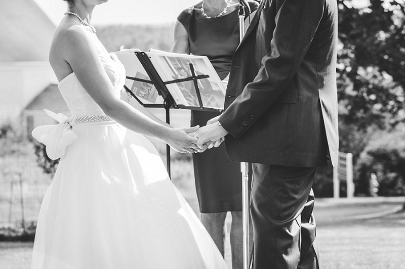 Bride and groom holding hands during ceremony at Wells Reserve black and white