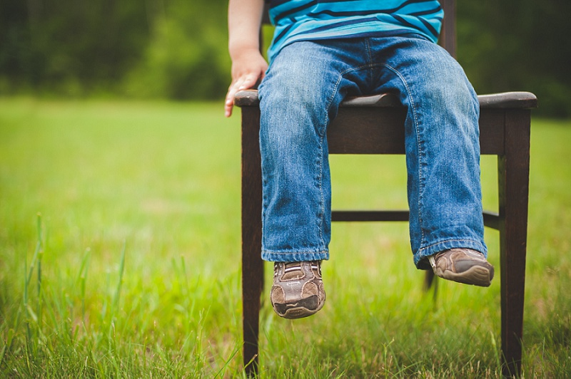 Young boy's legs sitting in a chair