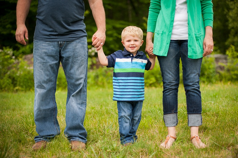 Father and mother hold their son's hands while standing