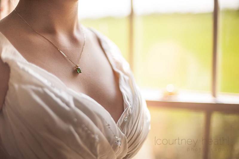 Bride wearing emerald necklace next to rustic window
