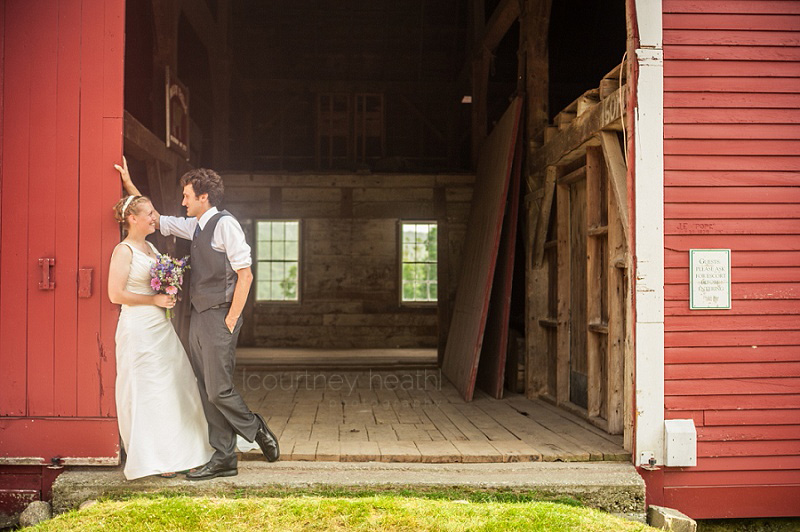 Groom and bride standing in red barn