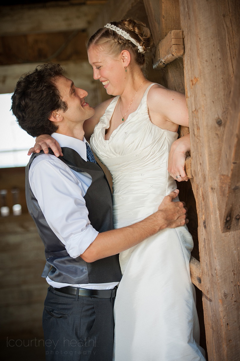Groom holds bride at waist in barn