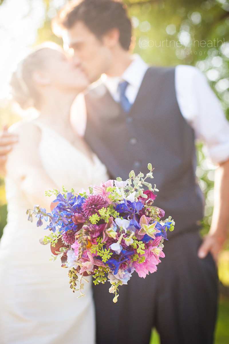 Bride and groom kiss with bouquet in focus