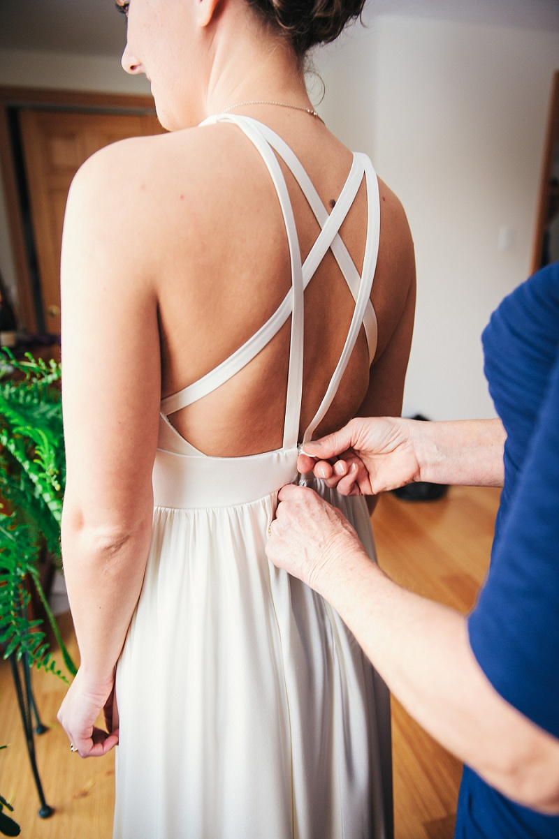 Bride's mother zipping up the wedding dress