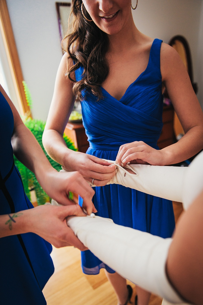 Bridesmaids helping button bride's gloves