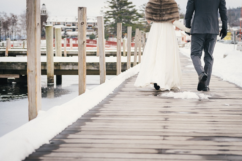Bride and groom holding hands at Meredith Town Docks