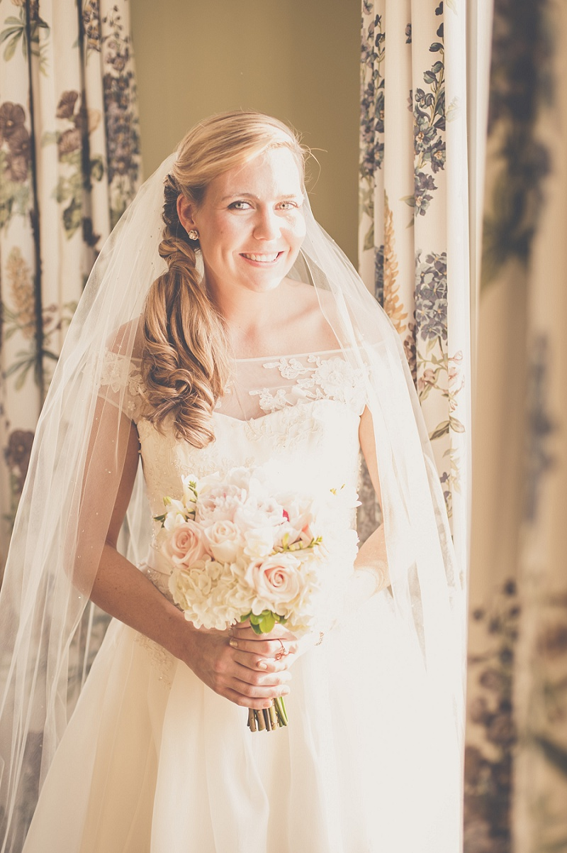 Bride smiling in wedding dress next to window at Mount Washington Hotel