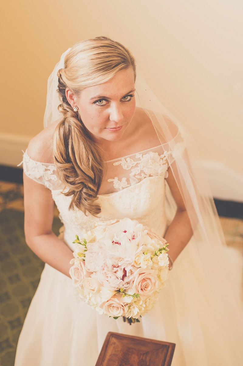 Beautiful bride holding bouquet and looking up in the stairwell of Mount Washington Hotel