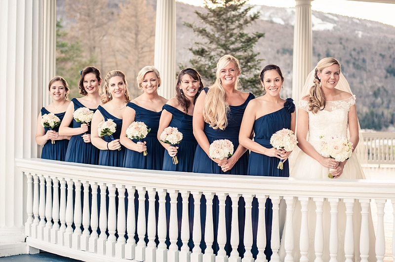 Bride and bridesmaids standing on the veranda at the Mount Washington Hotel in winter