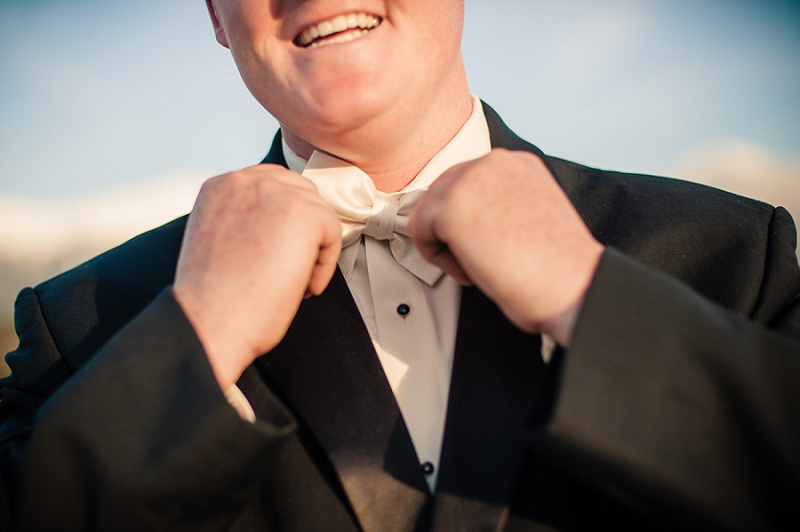 Groom smiling adjusting bow tie at the Mount Washington Hotel