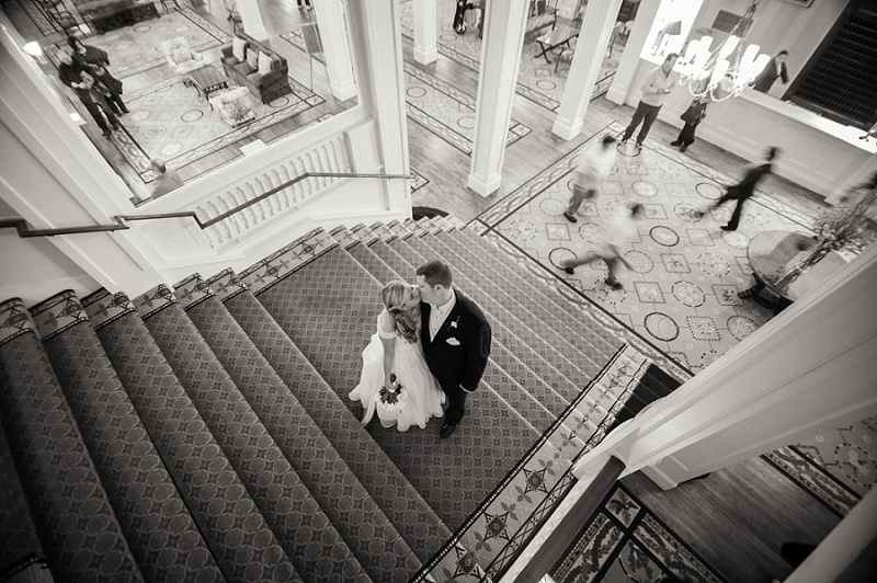 Bride and groom kissing in stairwell of Mount Washington Hotel black and white