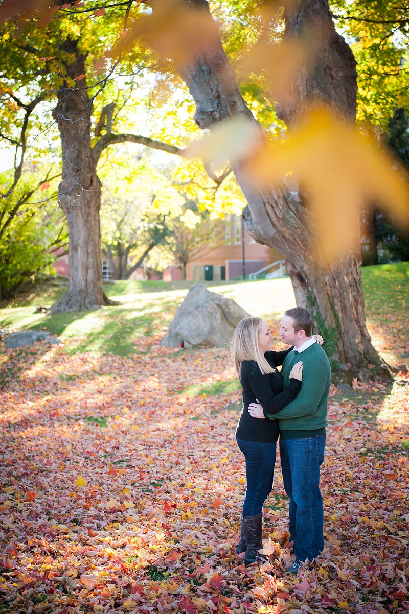Engaged couple standing in autumn leaves at UNH campus