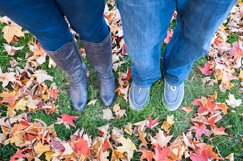 Engaged couple's boots and shoes standing in fall leaves