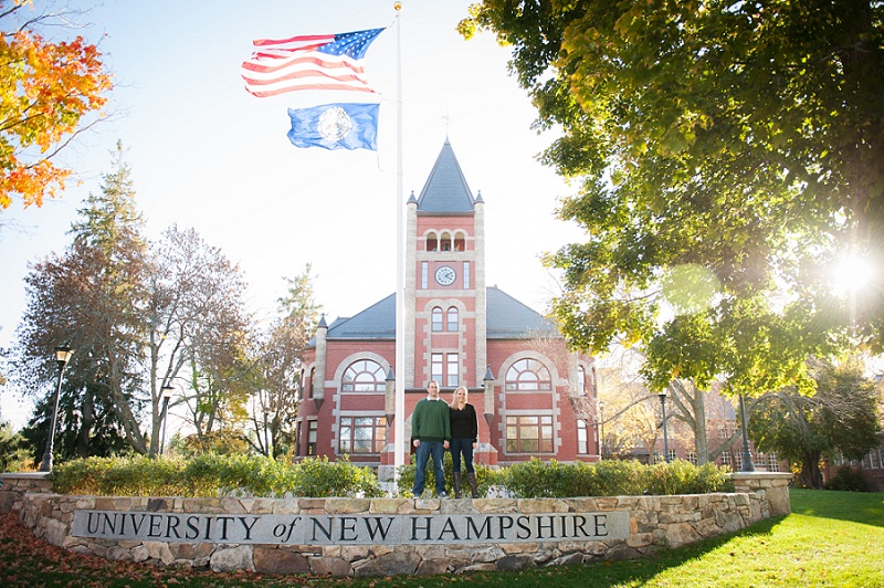 Engaged couple holding hands in front of UNH sign