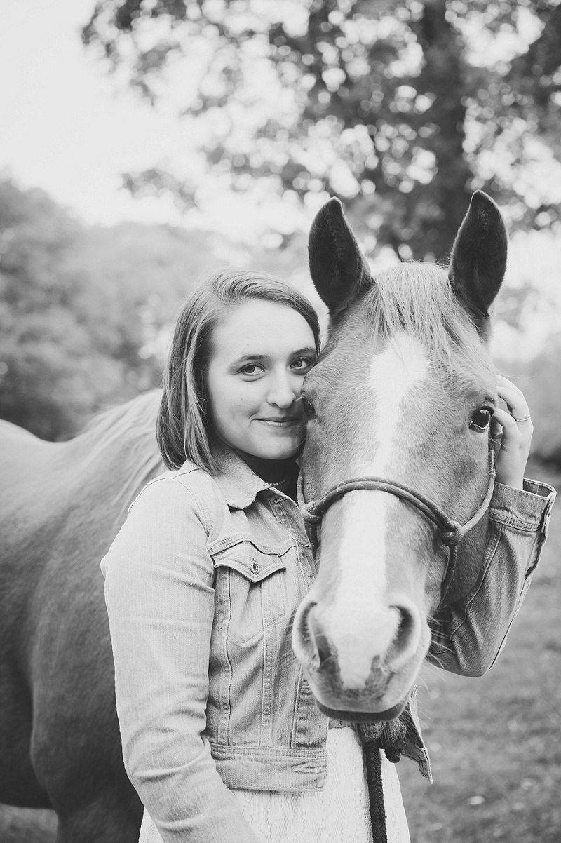 Senior portrait girl wrapping her arm around her horse