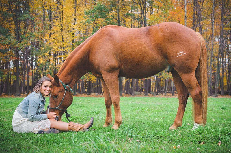 Girl sitting down with horse's head in her lap