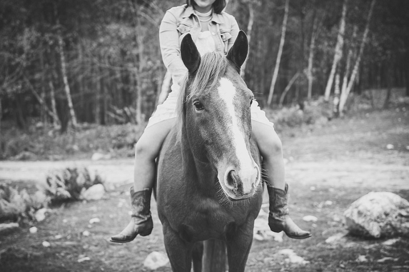 Girl riding a horse black and white