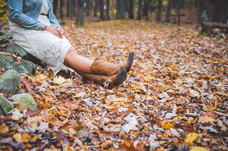 Cowgirl boots resting in autumn leaves