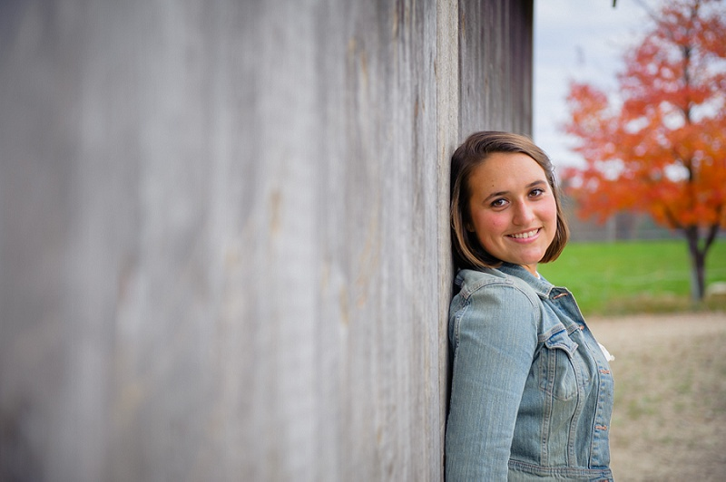 Senior portrait girl leaning against a barn