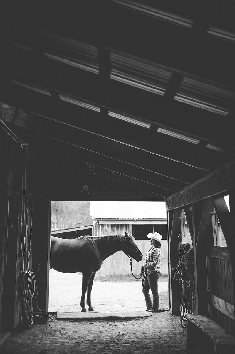 Senior portrait silhouette cowgirl and a horse in a barn