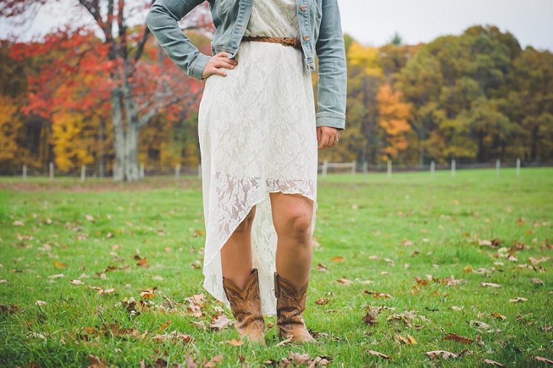 Cowgirl wearing boots standing in field hand on hip
