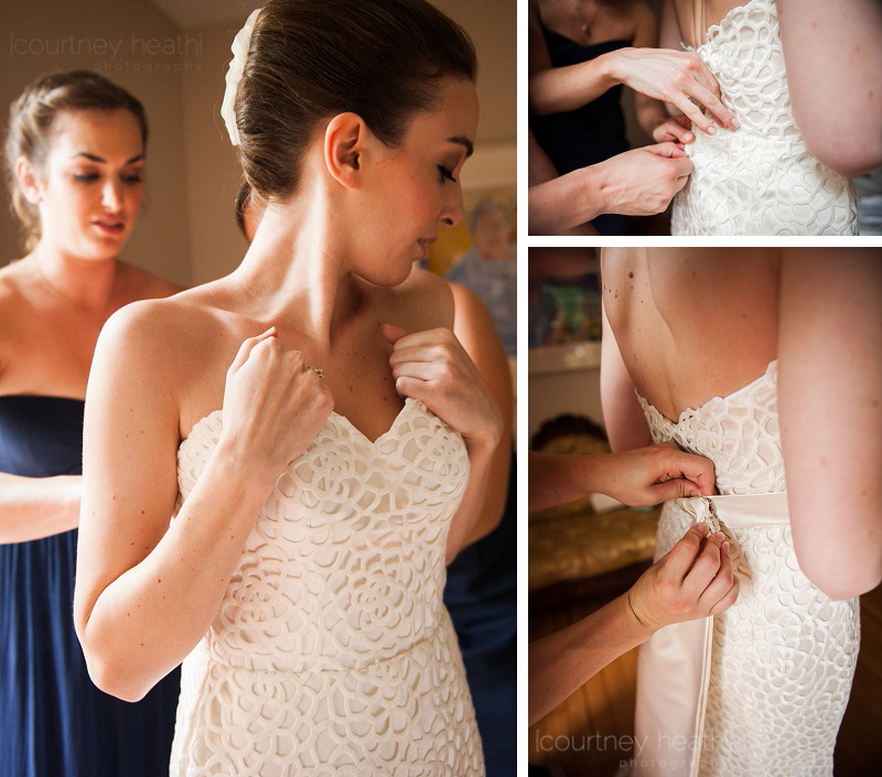 Maid of honor helping bride put on her dress