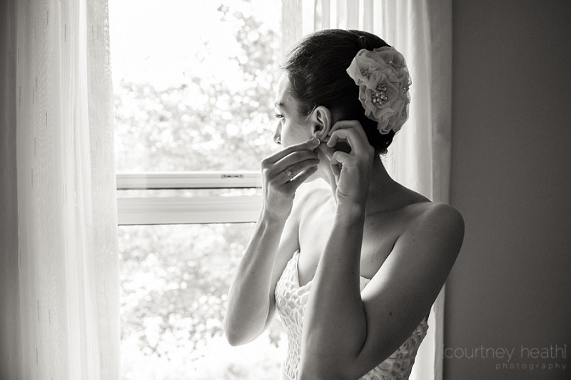 Bride standing in window putting on earring
