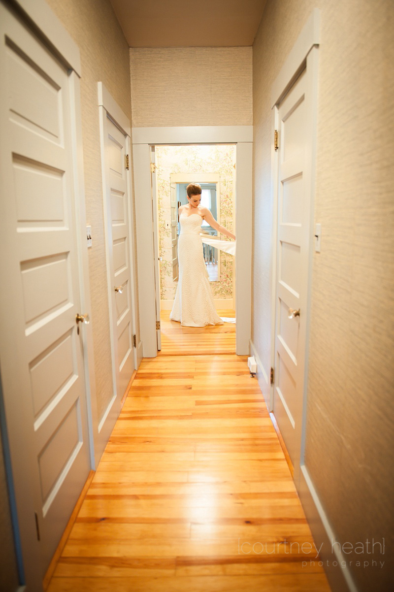 Wide angle shot of bride standing in hallway