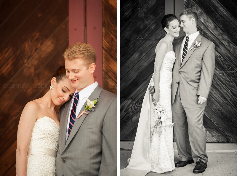 Bride and groom cuddle in front of boat house at Brewster Academy