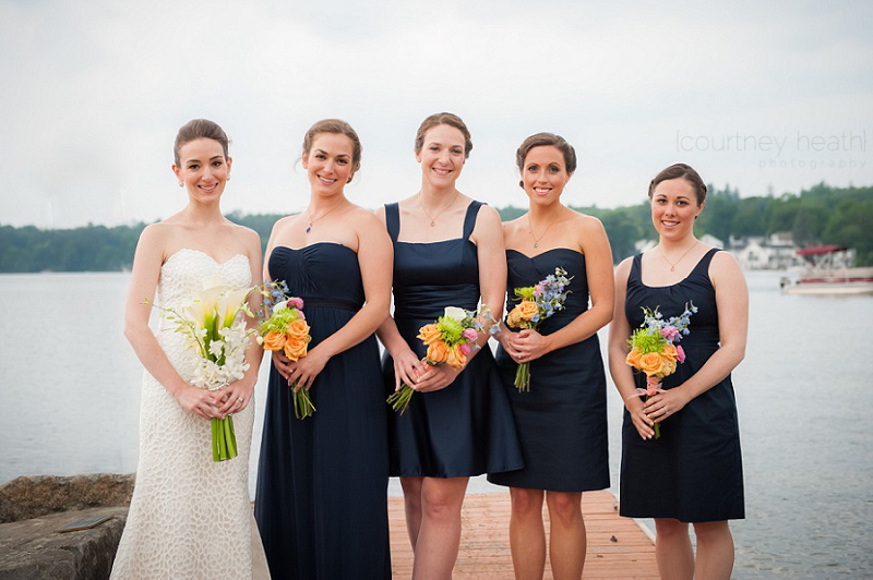 Bride and bridesmaids standing on dock at Brewster Academy