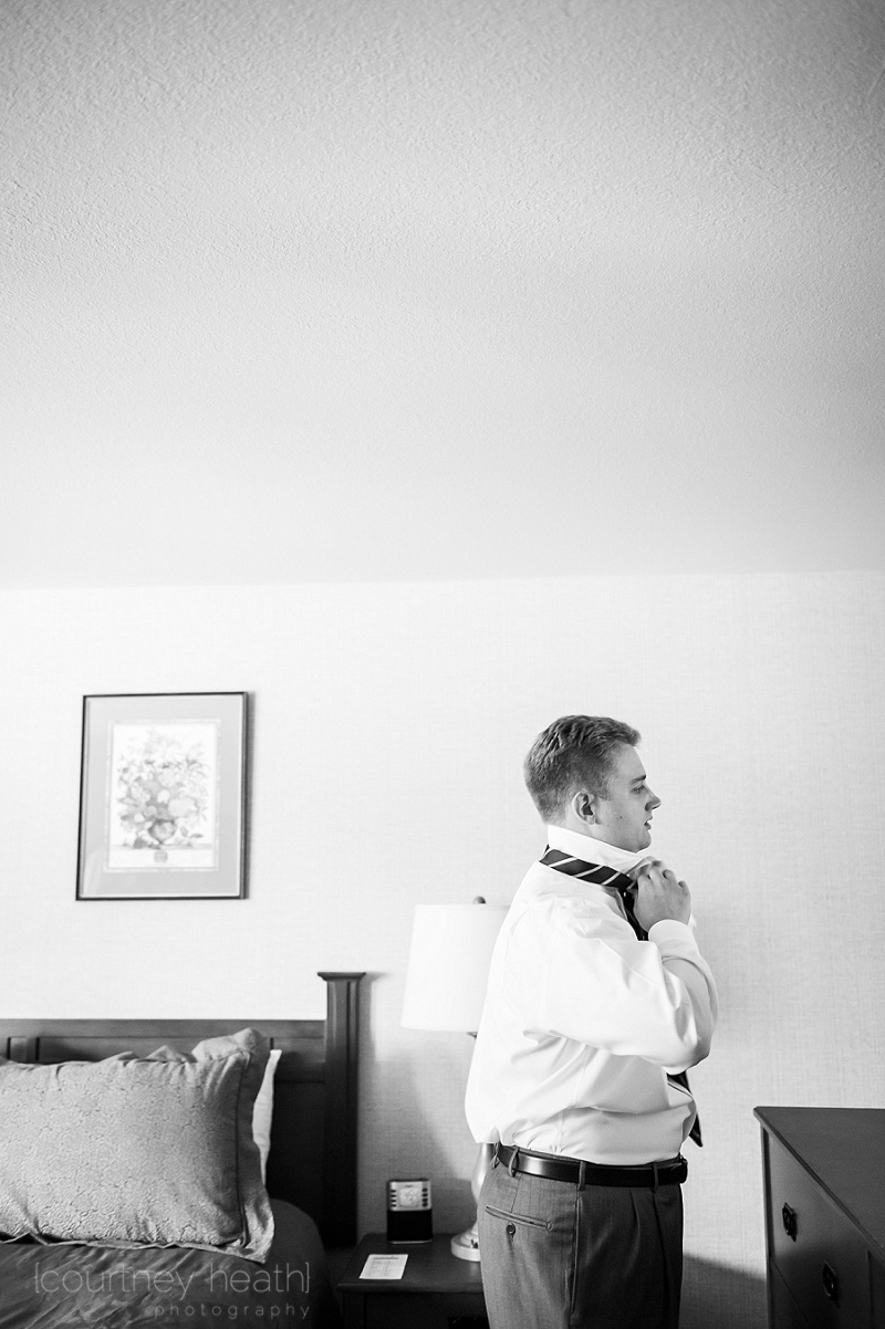 groom tying his tie black and white