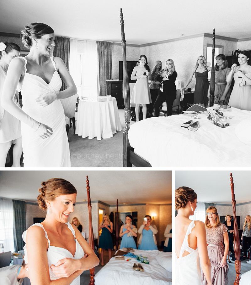 Bridesmaids watching bride put on her wedding dress