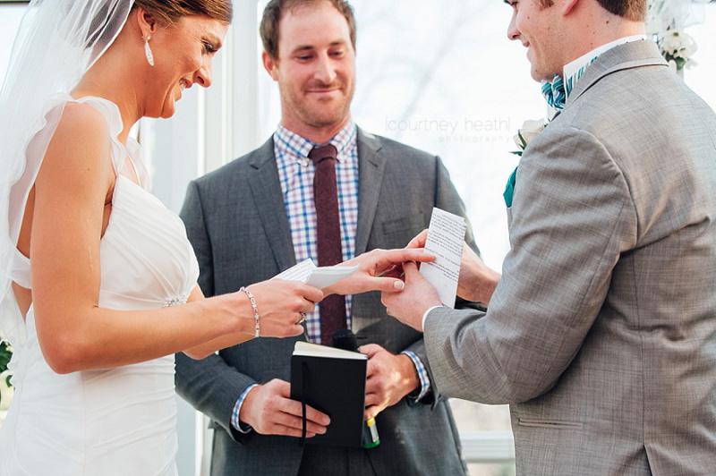 Groom putting wedding ring on bride's finger