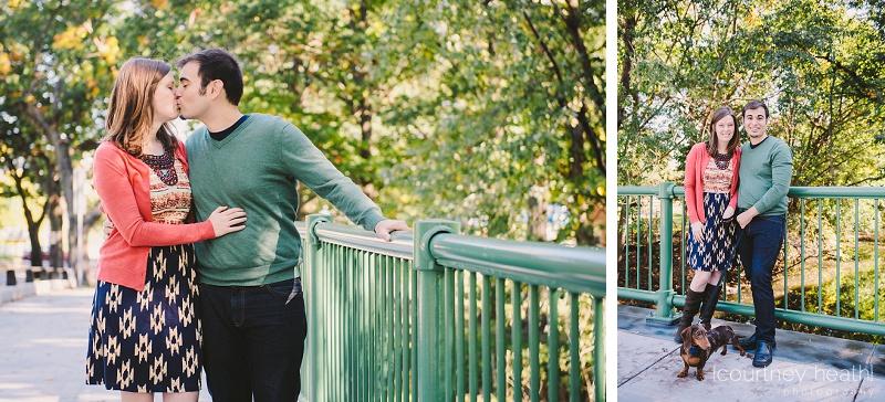 engaged couple holding dog while standing on bridge