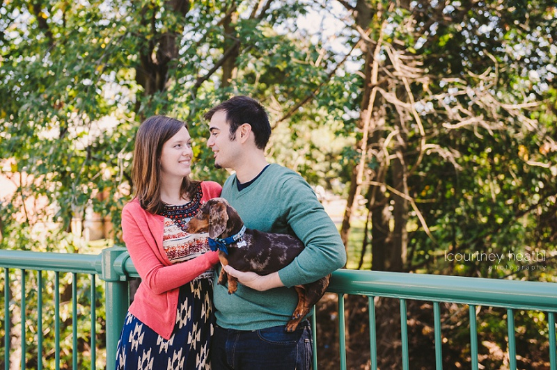 engaged couple looking at each other while holding dog on bridge